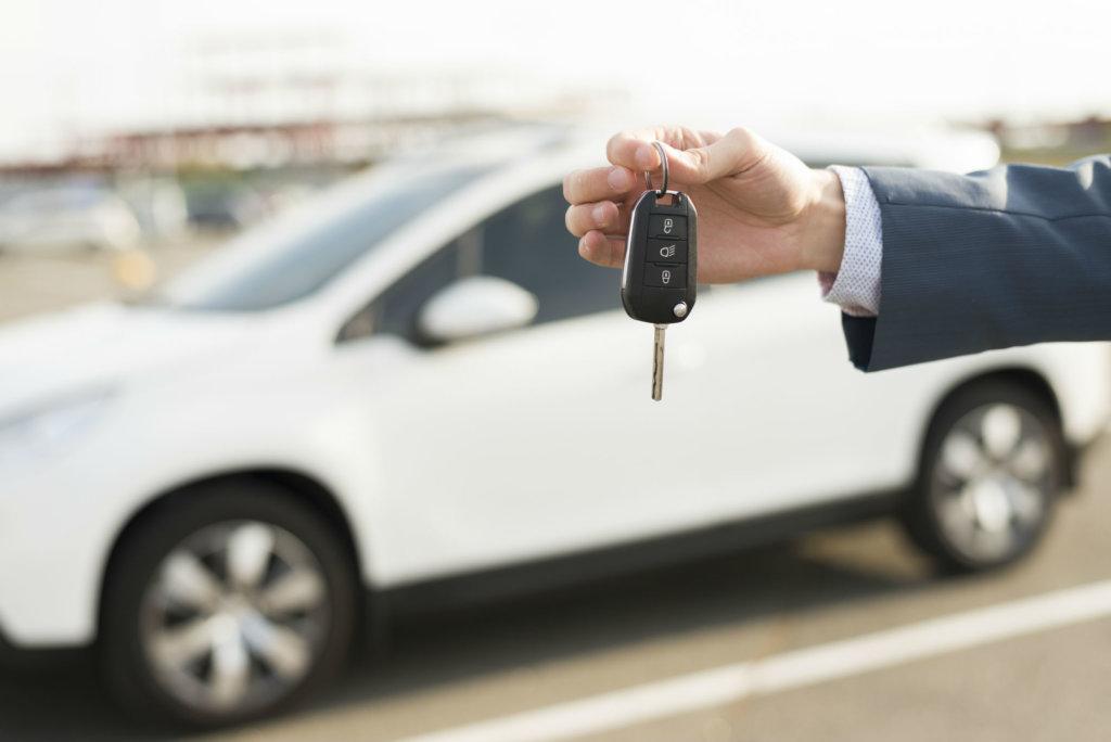 Louer une voiture, passage de clé au moment de la location avec voiture blanche en arrière plan