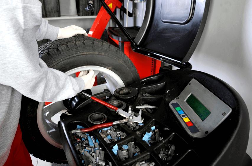 Mécanicien qui équilibre une roue de voiture